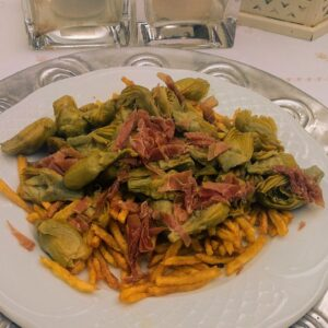 Alcachofas confitadas, con jamón y patatas paja.